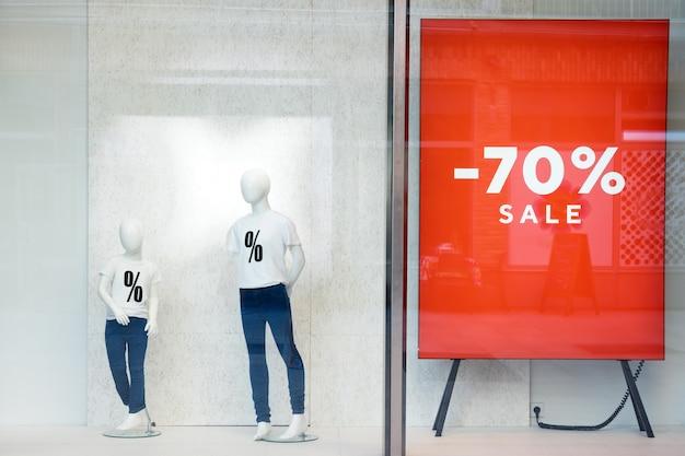 Vitrine de venda de compras com manequins vestindo camisetas com sinal de venda, manequins no conceito de loja, venda e moda.