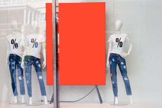 Vitrine de venda de compras com manequins vestindo camisetas com sinal do sal, manequins na loja, copyspase para conceito de texto, venda e moda.