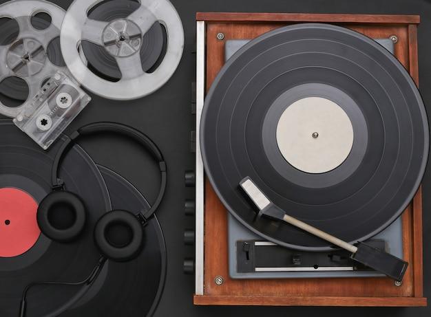 Vitrola de vinil retrô com discos, bobina magnética de áudio, fita cassete e fones de ouvido estéreo em fundo preto. vista do topo. postura plana