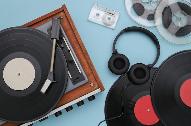Vitrola de vinil retrô com discos, bobina magnética de áudio, fita cassete e fones de ouvido estéreo em um fundo azul. vista do topo. postura plana