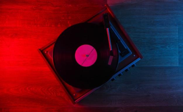 Vitrola de vinil retrô em piso de madeira com luz neon azul-vermelha