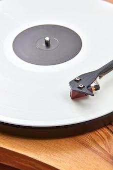 Vitrola vintage com disco de vinil em uma mesa de madeira.