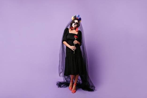 Viúva mexicana, tristemente, segurando uma rosa vermelha. foto de corpo inteiro de uma mulher vestida de preto com véu de noiva.