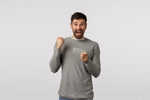 Viva, sim, eu passei de nível. feliz e alegre homem barbudo bonito de suéter cinza, bomba de punho, apertar a mão em movimento de celebração, sorrindo, segurando o smartphone, jogo terminado, recebeu ótimas notícias