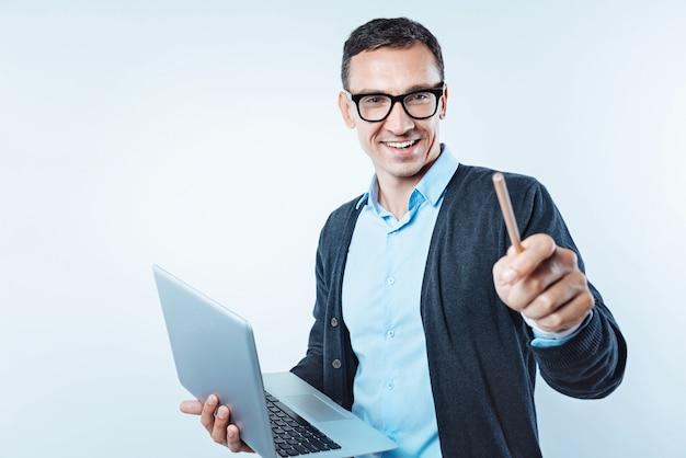 Vivência tecnológica. esperto relaxado fingindo tocar uma parede transparente enquanto trabalhava em um projeto de negócio sério e segurando seu laptop sobre o fundo.