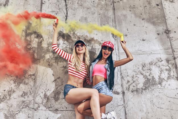 Vivendo uma vida brilhante. vista de baixo ângulo de duas jovens alegres segurando bombas de fumaça e sorrindo enquanto posam contra a parede de concreto