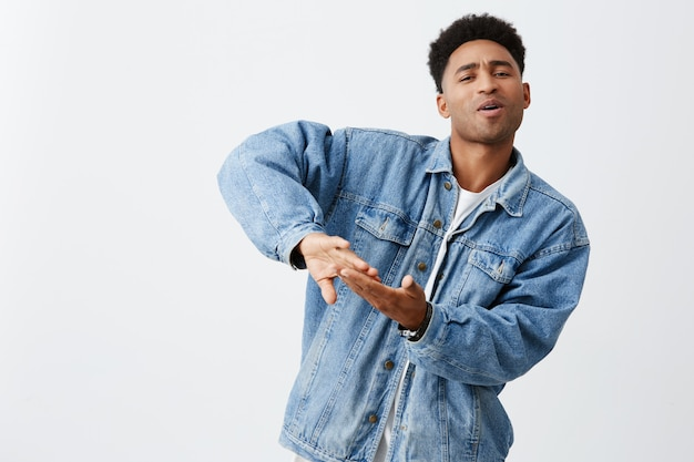 Vivendo uma vida rica. emoções positivas. retrato de jovem homem de pele negra atraente com penteado afro em jaqueta jeans e camiseta branca, jogando dinheiro fora para o videoclipe, se divertindo com os amigos