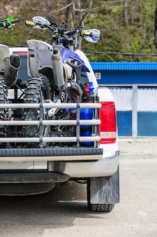Viwe traseiro com duas motocicletas de sujeira na traseira do caminhão com equipamento de segurança em ambiente residencial.