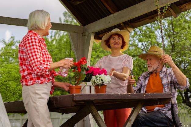 Vizinhos juntos. mulheres idosas e animadas regando flores enquanto um homem corta galhos