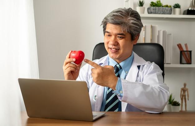 Vlog blogueiro médico asiático influenciador gravando videoblog para educar sobre doenças cardíacas para pacientes