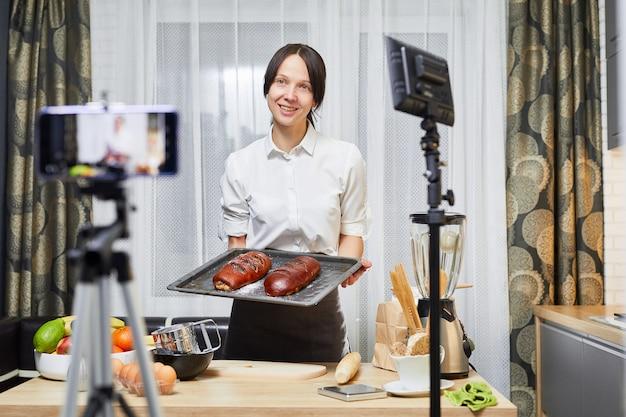Vlog culinária. blog de culinária. mulher caucasiana, cozinhar e mostrar o cozimento para mídias sociais. gravação de vídeo na cozinha.