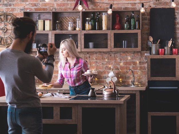 Vlog de comida. tiro de podcast culinário. homem com câmera de gravação de mulher com bolos e doces frescos.