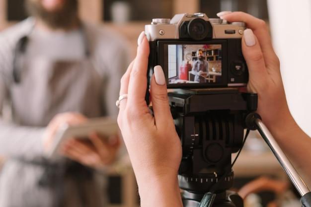 Vlog de comida. tiro de podcast culinário. mulher com avental de homem de gravação de câmera. tablet nas mãos.