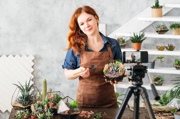Vlog especialista em decoração natural. mulher mostrando na câmera do smartphone como fazer florarium com suculentas.