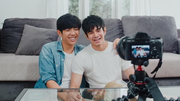 Vlog gay asiático novo dos pares do influenciador dos pares em casa. os homens lgbtq coreanos adolescentes felizes relaxam o divertimento usando o upload de vídeo do vlog de registro de câmera nas mídias sociais enquanto estão deitados no sofá na sala de estar em casa.