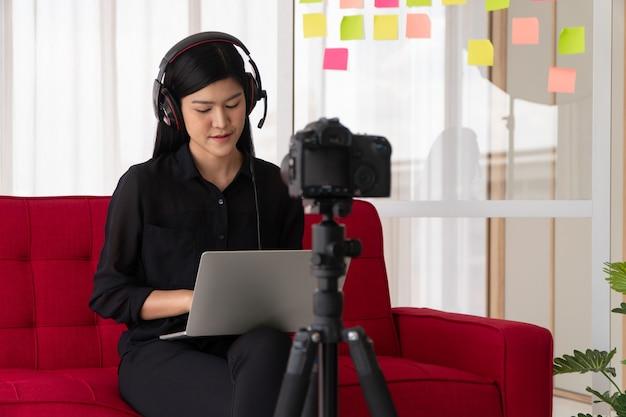 Vlog mulher asiática blogueira influenciadora sentada no sofá em casa gravando videoblog para ensinar aluno