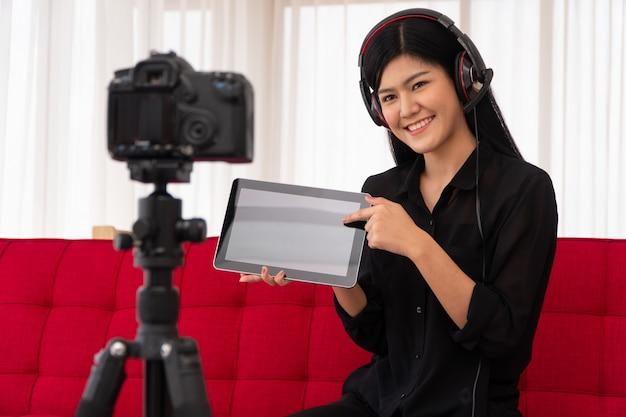 Vlog mulher asiática blogueira influenciadora sentada no sofá em casa gravando videoblog para ensinar alunos