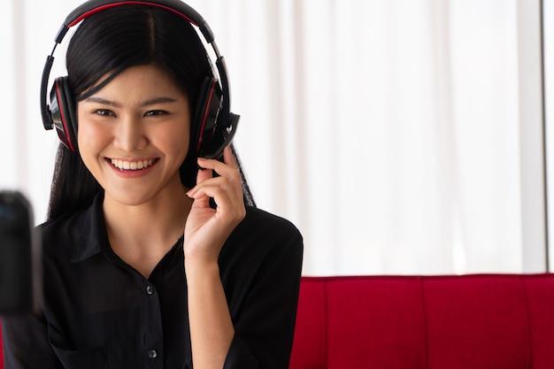 Vlog mulher asiática blogueira influenciadora sentada no sofá em casa gravando videoblog para ensinar