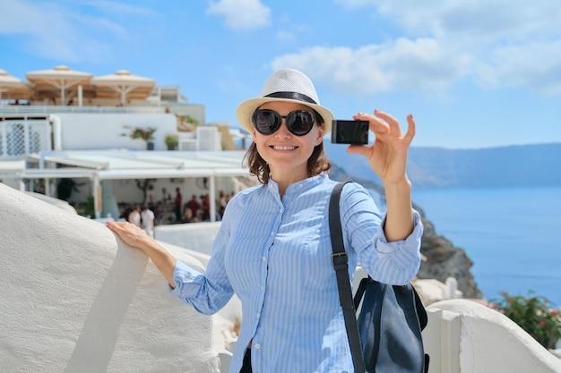 Vloger de viagem de mulher viajando na aldeia grega de oia, na ilha de santorini, filmando um vídeo com a câmera aktion, arquitetura de fundo branco, mar, céu nas nuvens