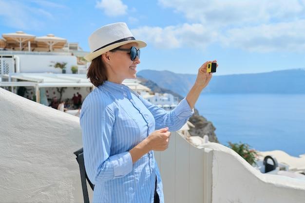 Vloger de viagem de mulher viajando na aldeia grega de oia, na ilha de santorini, filmando um vídeo com a câmera aktion, arquitetura espacial branca, mar, céu nas nuvens