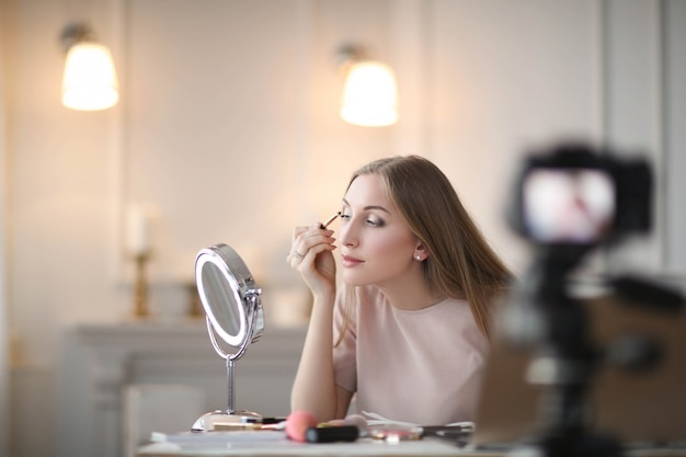 Vlogger de beleza. jovem gravando um tutorial de maquiagem
