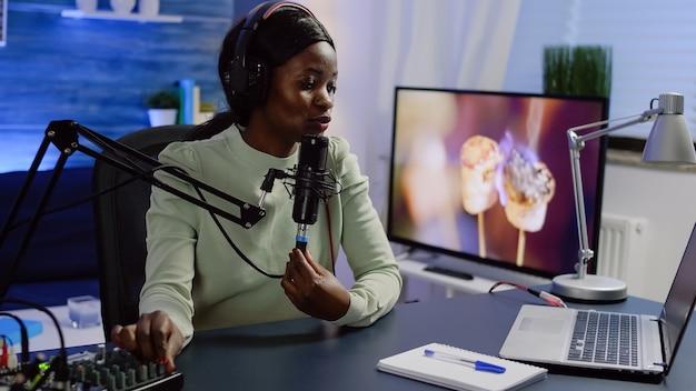 Vlogger de mídia social falando com seguidores em podcast online usando microfone e fone de ouvido profissional