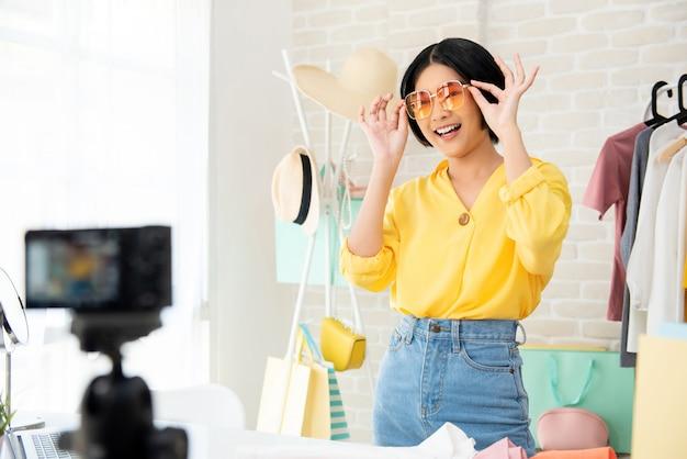 Vlogger de moda jovem mulher asiática experimentando roupas e acessórios