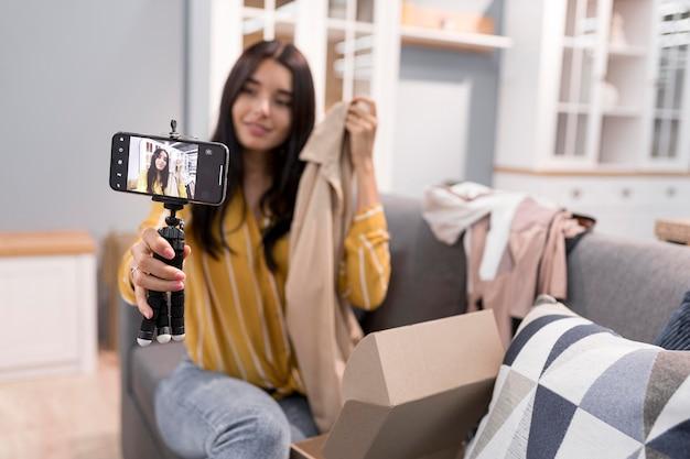 Vlogger em casa com roupas para desembalar no smartphone