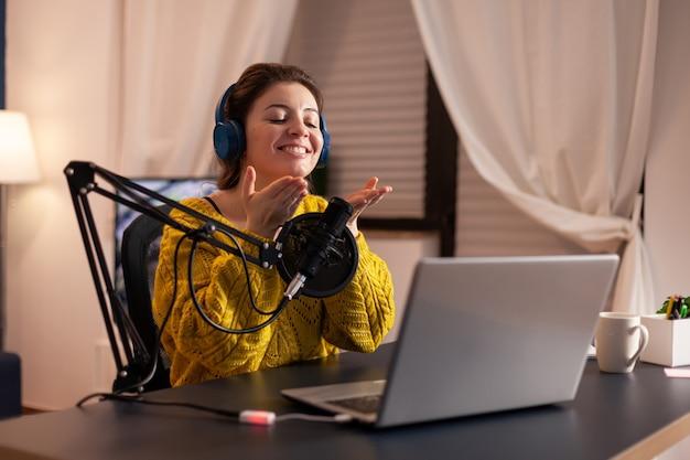 Vlogger falando com o seguidor ao vivo usando um microfone profissional usando fones de ouvido
