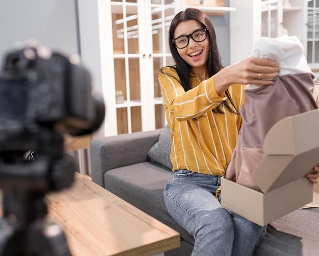 Vlogger feminina em casa com a câmera tirando as roupas da caixa