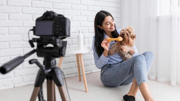 Vlogger feminina em casa com câmera e cachorro