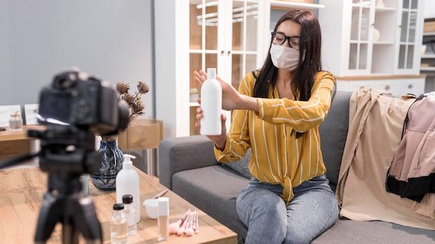 Vlogger feminina em casa com câmera e garrafa