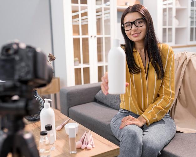 Vlogger feminina em casa com garrafa e câmera