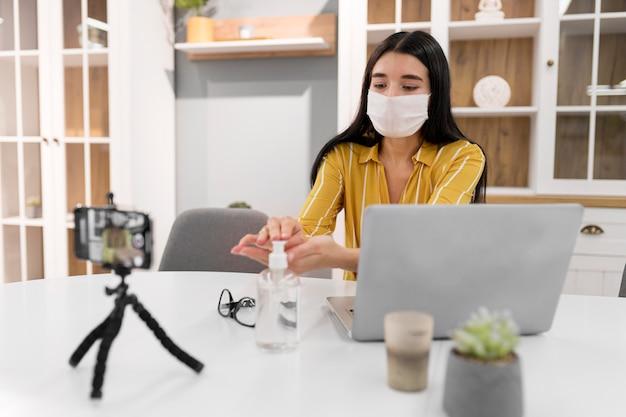 Vlogger feminina em casa com laptop e desinfetante para as mãos