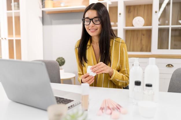 Vlogger feminina em casa com laptop e produtos