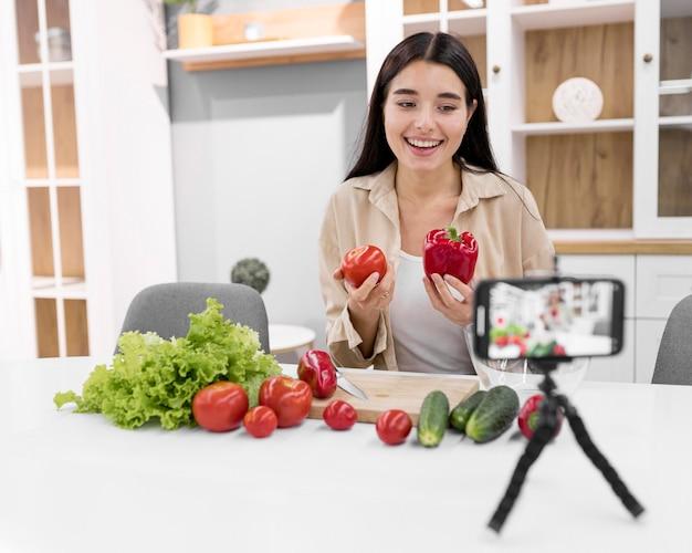 Vlogger feminina em casa com smartphone e vegetais