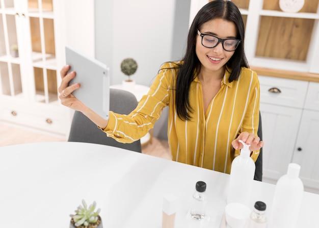Vlogger feminina em casa com tablet e produtos
