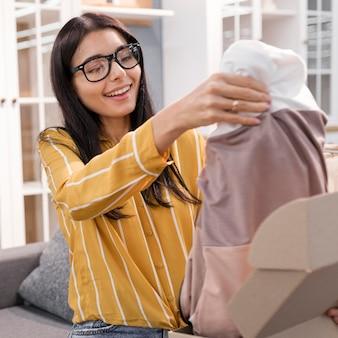Vlogger feminina em casa desembalando roupas