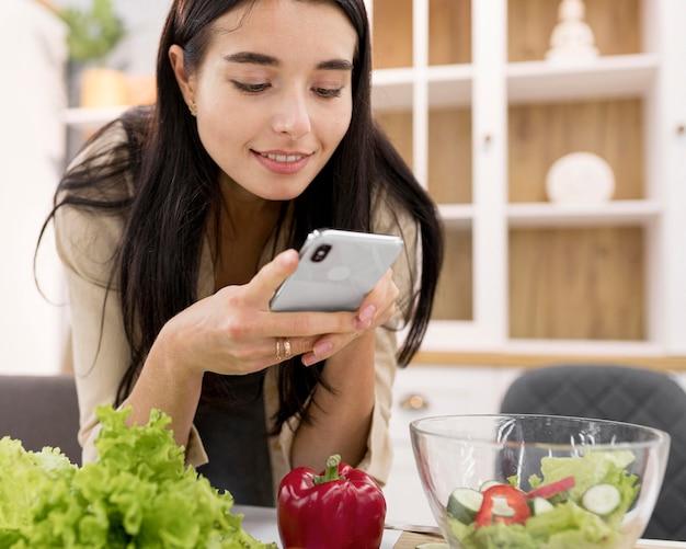 Vlogger feminina tirando fotos em casa com smartphone