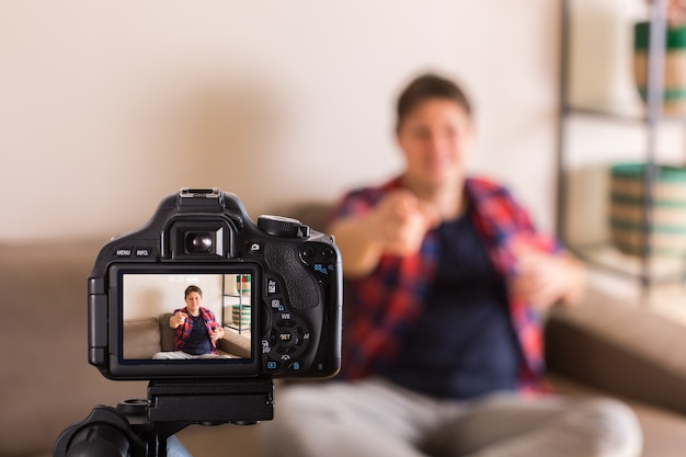 Vlogger gravando vídeo de mídia social sentado no sofá