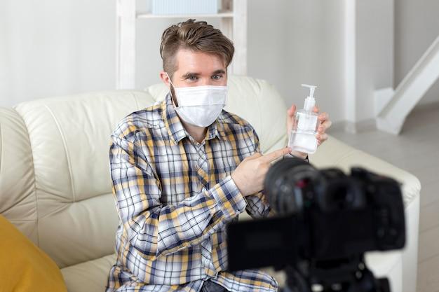 Vlogger gravando vídeo em casa com desinfetante para as mãos