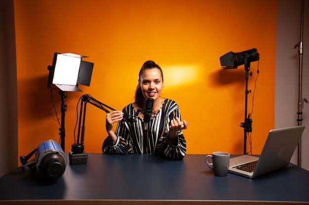 Vlogger gravando vídeo usando microfone profissional