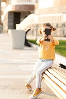 Vlogger infantil fazendo videochamada, conversando com amigos ao ar livre. blogueiro de turismo infantil tirando fotos de selfies para redes sociais no telefone próximo ao ponto de atração turística.