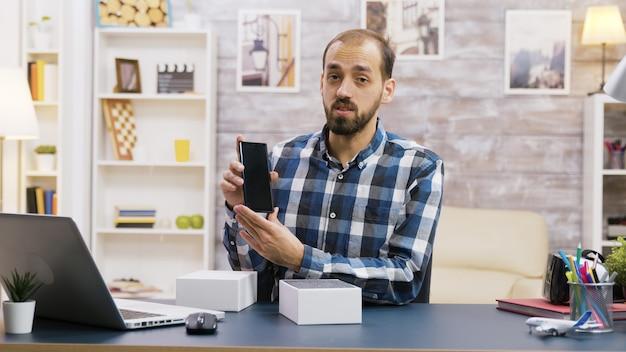 Vlogger masculino gravando o unboxing do novo telefone. criador de conteúdo famoso.