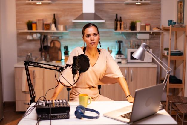 Vlogger olhando para a câmera enquanto fala no microfone durante um podcast de entretenimento. creative online show. produção no ar, transmissão pela internet, transmissão de conteúdo ao vivo.