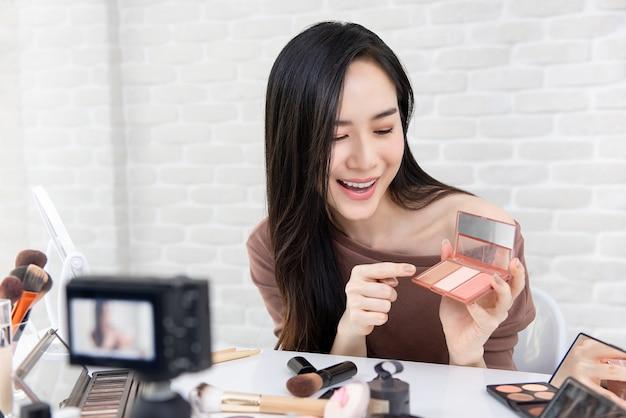 Vlogger profissional da beleza da mulher asiática que grava o vídeo tutorial da composição cosmética