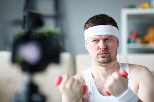 Vlogger sério fazendo exercício com halteres