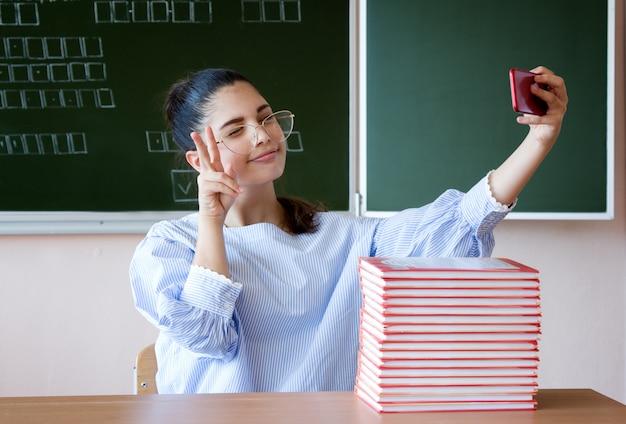 Vlogger transmitir online. estudante localização contra lousa na sala de aula e fazendo o sinal da vitória