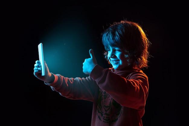 Vlogging com smartphone, polegar para cima. retrato do menino caucasiano na parede escura em luz de néon. lindo modelo cacheado. conceito de emoções humanas, expressão facial, vendas, anúncio, tecnologia moderna, gadgets.