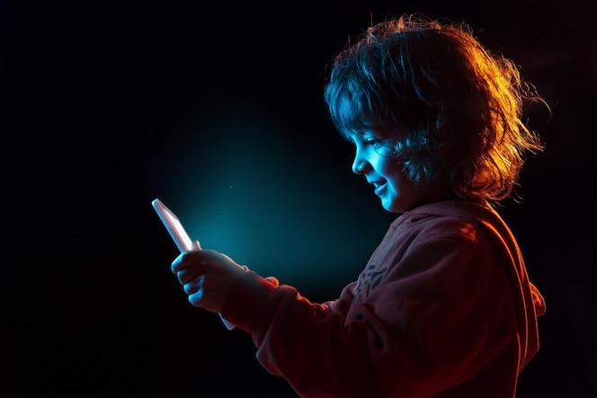 Vlogging com tablet, jogar. retrato do menino caucasiano em fundo escuro do estúdio em luz de néon. lindo modelo cacheado. conceito de emoções humanas, expressão facial, vendas, anúncio, tecnologia moderna, gadgets.